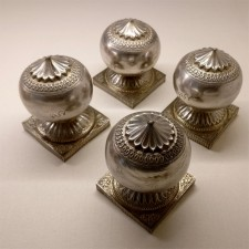 Silver weights meant to weight down corners of carpets